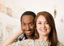 Happy interracial couple headshots posing happily and smiling, woman holding boyfriends head with her hand, white studio Royalty Free Stock Photos