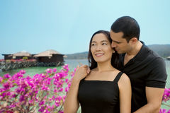 Happy interracial couple in love at sea side with bungalow backg. Round .Summer holidays,vacation, travel and dating concept. Asian woman,Caucasian man Royalty Free Stock Photography