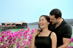 Happy interracial couple in love at sea side with bungalow backg. Round .Summer holidays,vacation, travel and dating concept. Asian woman,Caucasian man Stock Images