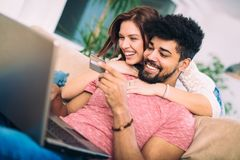 Happy interracial couple shopping online. At home, using credit card, laughing royalty free stock images