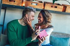 Interracial couple sitting in cafe bar. Man giving gift to his girlfriend. Happy interracial couple sitting in cafe bar. Man giving gift to his girlfriend stock images
