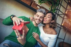 Man giving gift to his girlfriend. Happy  interracial couple sitting in cafe bar. Man giving gift to his girlfriend Royalty Free Stock Photos