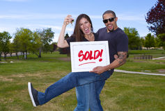 Happy Interracial Couple with Sold Sign Royalty Free Stock Photo