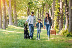 Happy interracial family with picnic basket walking with dog in forest. Young happy interracial family with picnic basket walking with dog in forest royalty free stock image