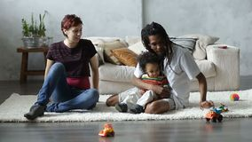 Happy interracial family playing with car toys stock footage