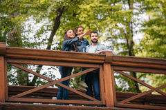 Happy interracial family standing on wooden bridge, while mother pointing somewhere Royalty Free Stock Photo