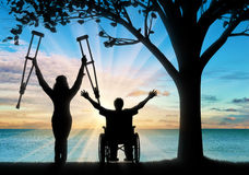 Happy invalids with crutches and in wheelchair near sea and tree Royalty Free Stock Image