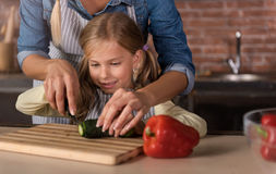 Happy involved girl cutting a cucumber with her mother Royalty Free Stock Image