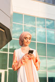 Happy islamic woman using smart phone. Outdoors Stock Images