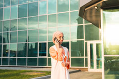 Happy islamic woman using smart phone. Outdoors Royalty Free Stock Photo