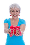 Happy isolated older woman holding a present. Royalty Free Stock Photos