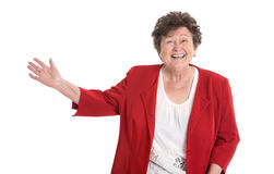 Happy isolated older woman in red presenting with hand. Royalty Free Stock Photography