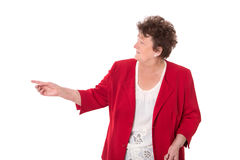 Happy isolated older woman in red presenting with hand. Royalty Free Stock Image