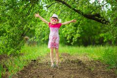 Happy ittle girl in bright dress and funny sunglasses walk in summer garden. Happy ittle girl in bright dress and funny sunglasses walk in garden royalty free stock images