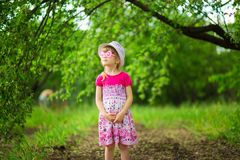 Happy ittle girl in bright dress and funny sunglasses walk in summer garden. Happy ittle girl in bright dress and funny sunglasses walk in garden stock photos
