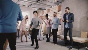 Happy Japanese employee doing funny dance moves at casual office celebration party. Team celebrates success slow motion. stock video