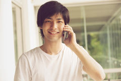 Happy japanese man on the phone. Happy japanese man smiling on the phone royalty free stock photos
