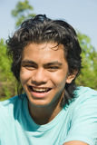 Happy jogger portrait. Closeup portrait of sweaty happy and smiling Indian teenage jogger after the exercise with curly black hair outdoors Royalty Free Stock Photos