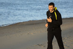 Happy jogging on the beach. The smiling happy man is jogging on the beach with earphones Stock Photo