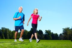 Happy jogging couple. Happy senior couple jogging in the park royalty free stock images