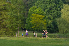 Happy jogging family. OLDENZAAL, NETHERLANDS - MAY 27, 2016: Unknown parents with some children jogging in a park Stock Images