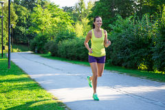 Happy jogging woman running in park Stock Images