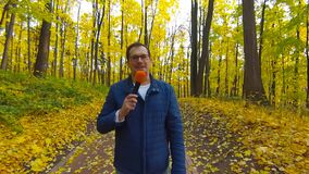 Happy Journalist is reporting from the autumn park for TV stock footage