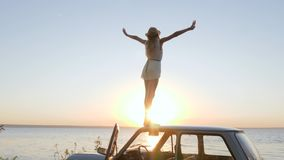 Happy Journey on automobile, Young woman admires sundown on Embankment, girl standing on roof Car with Widely spread stock footage