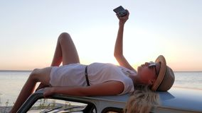 Happy Journey, young woman lying on rooftop auto makes pictures on phone, female make selfie photo at mobile on retro stock footage