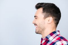 Happy, joy, fun, youth concept. Side profile portrait of young h. Andsome man in casual shirt with beaming smile, near copy space royalty free stock photos