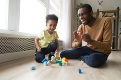 Happy joyful african dad and toddler son laughing playing together royalty free stock photo