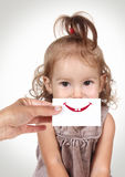 Happy joyful baby girl hiding her face by hand with smile and te Stock Images