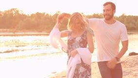 Couple in love on beach. Happy joyful couple in love walk on beach near water / river in spring / summer. Date concept stock footage