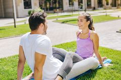 Happy joyful couple sitting on the yoga mat. In love. Happy joyful couple sitting on the yoga mat while looking at the each other royalty free stock photos