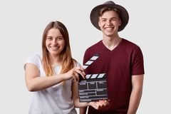 Happy joyful couple stand closely, hold clapperboard in front, prepare for next scene and take, expresses positive emotions in. Cinema, isolated over white stock photos