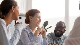 Happy joyful diverse business people talking laughing at funny joke stock photography