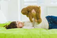 Happy joyful and dreaming girl holding teddy bear indoor Stock Images