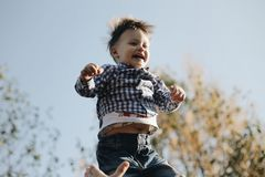 Happy joyful father having fun throws up in the air child. Son is laughing. stock photography