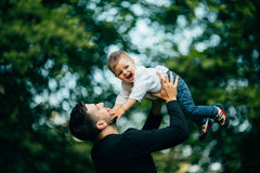 Happy joyful father having fun throws up in the air. His small child, family, father's day - concept Royalty Free Stock Photo