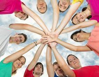 Happy joyful friends forming a circle. With their hands in center Stock Photography