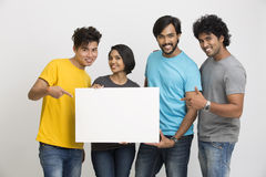 Happy joyful group of friends displaying white boad Royalty Free Stock Images