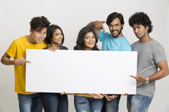 Happy joyful group of friends displaying white board Royalty Free Stock Photo