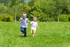 Happy joyful kids running on the grass Stock Images