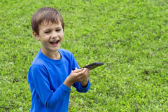 Happy joyful laughing child with mobile phone outdoors. Childhood, technology, leisure concept Royalty Free Stock Photo