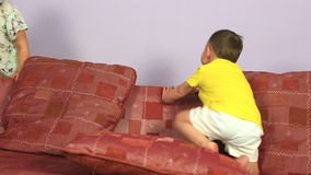 Happy joyful little brother and sister playing and jumping on couch. stock footage