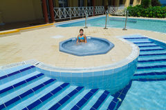 Happy joyful little girl enjoying her leisure time and relaxing in outdoor small Jacuzzi Royalty Free Stock Image