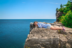 Happy, joyful little girl lying and relaxing on the edge of high cliff above gorgeous amazing Cyprus lake Stock Images
