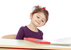 Happy joyful little girl reading a book while Stock Photo