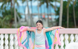 Happy joyful little girl standing on the balcony against tropical beach and ocean background Stock Images