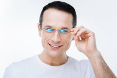 Happy joyful man fixing his glasses. Bad eyesight. Happy positive joyful man smiling and fixing his glasses while looking at you Royalty Free Stock Photo